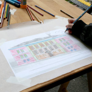 Lähikuva piirustuksesta, jota lapsi värittää. Piirustuksessa on museon uusrenessanssirakennus ja siihen kuviteltu laajennus.