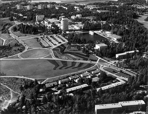 Ilmakuva Tapiolan keskustasta. Edustalla kerros- ja rivitaloja, sen takana teitä ja niittyaukeaa ja näiden takana Tapiolan keskusallas torneineen.