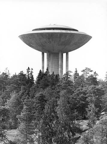 Eksteriöörivalokuva Haukilahden vesitornista. Etualalla on mäntymetsää, jonka keskeltä vesitorni kohoaa.