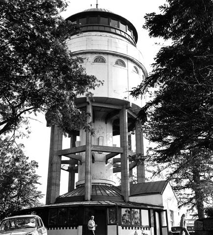Valokuva vesitornin juurelta. Kuvassa betonipalkein tuettu vesitorni jonka alaosassa on liiketilaa.