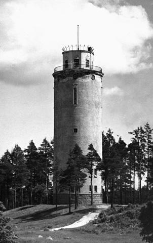 Eksteriöörikuva vesitornista. Kuvassa kartionmuotoinnen vesitorni seisoo mäntyisen rinteen päällä.
