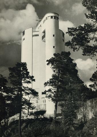 Eksteriöörikuva Karjaan vesitornista. Kuvassa valkoinen funkistyylinen torni seisoo mäntyisen kallion päällä.