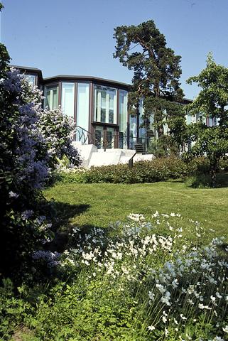 Kuva kesäisestä Mäntyniemen puutarhasta. Kuvasssa rinteessä syreenien ja muiden kukkien peittämä puutarha ja taaempana Mäntyniemen päärakennus.