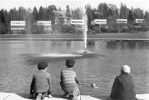 Lapsia Tapiolan keskustassa, vesialtaan edustalla. Kuvassa etualalla kolme poikaa selin kuvaajaan päin, taaempana vesiallas suihkulähteineen, jonka takana pienkerrostaloja ja korkeampia kerrostaloja.