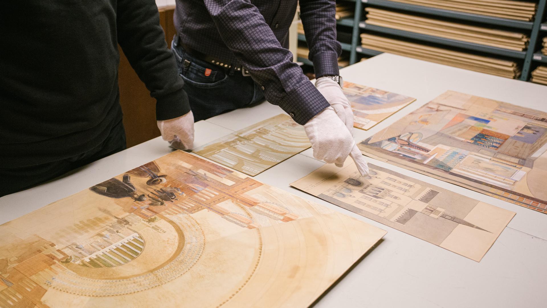 Arkiston asiantuntijat tutkimassa Eliel Saarisen alkuperäispiirusuksia Arkkitehtuurimuseon arkistossa